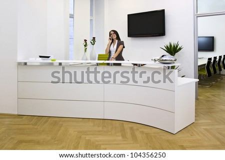 Front desk lady doing her job very well and cheerfully. The black space on the TV-sreen could be used for any logos, some label signs or any graphic additions. - stock photo