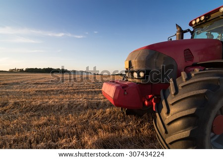 Front detail of an agriculture tractor and tow trailer waiting to be filled at grain campaign at sunset on a stubble field