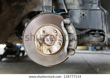 Front disk brake on car in process of damaged tyre replacement. The rim is removed showing the front rotor and caliper. - stock photo