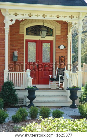 Front door entrance to victorian home with red doors, red brick, porch and two iron urns - stock photo