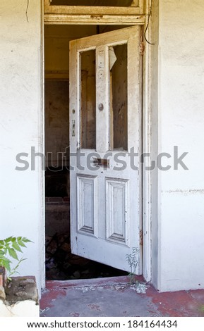 front door of a broken old house with white paint on the wood