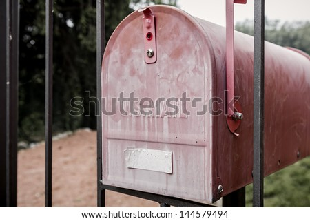 Front door of a red mailbox mounted on the house gate - stock photo