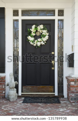 Front door of an upscale home/Vertical shot of a front door of a home with a wreath, brick flooring and reflection in the windows - stock photo