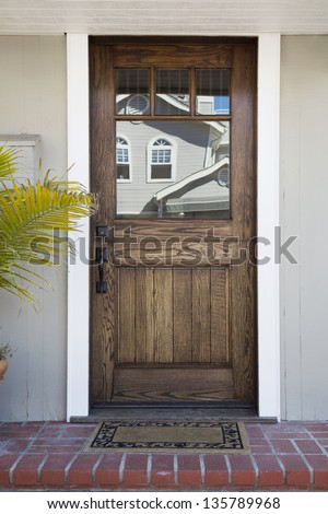 Front door of an upscale home/Vertical shot of a wooden front door of an upscale home with reflection in the windows and view of doormat, brick flooring and palm tree - stock photo