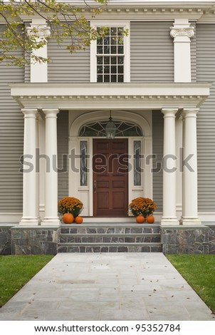Front Door of Home showing two pillars with arch and twin flowerpots with four pumpkins, 2 on each side. Shows stone tile walkway leading to front entrance. - stock photo
