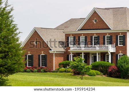Front elevation of a large single family modern US house with landscaped gardens and lawn on a warm sunny summers day - stock photo