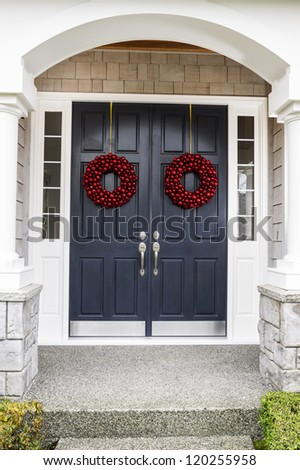 Front entrance of home door decorated with red ball wreaths for the holiday