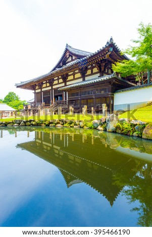 Front entrance of Sangatsu-do Hall reflected in the pond on a sunny morning in the Todai-ji temple complex at Nara, Japan. Vertical - stock photo