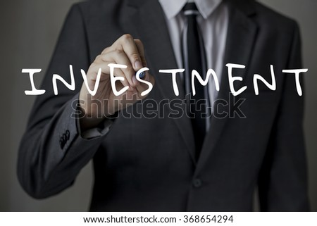 "Front faced businessman is writing ""INVESTMENT"" on the board (focus on hand, blur out the suit)."