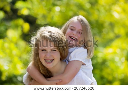 Front forward view, with focus on older sister, of oldest sister holding younger sister on her back while laughing together - stock photo