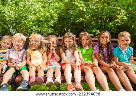 Front group portrait of group of kids sitting on the bench in the park, boys and girls 3-5 years old - stock photo