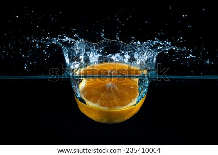 Front half orange falling into the water with blue splash and air bubbles with black background - stock photo