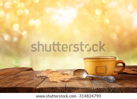 front image of coffee cup over wooden table and autumn leaves in front of autumnal sunset background  - stock photo