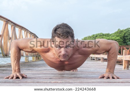 Front low angle of muscular shirtless Caucasian man performing push ups on wooden dock at beach