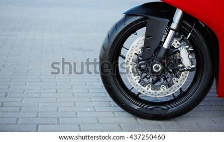 Front motorcycle disk breaks and tire in close up - stock photo