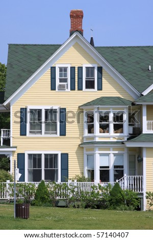 Front of a yellow house and blue sky - stock photo