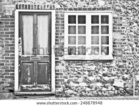Front of an old cottage with peeling paint on the door and window - stock photo