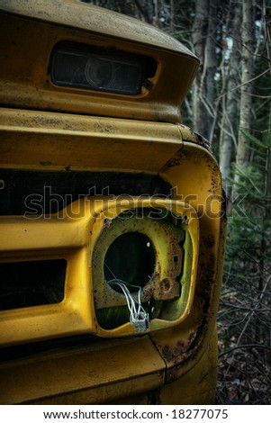 Front of an old school bus abandoned in the forest