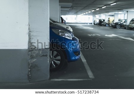Front of blue car on lot in parking garage.