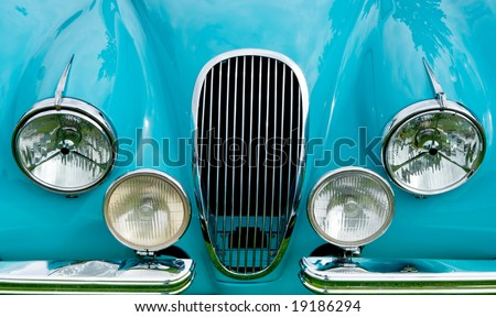 Front of blue classic car showing grill, headlights and fender. - stock photo