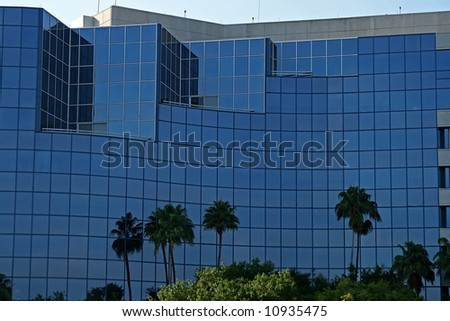 front of blue reflective tropical office building - stock photo