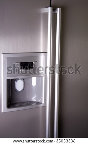 Front of modern refrigerator that can make ice cubes - stock photo