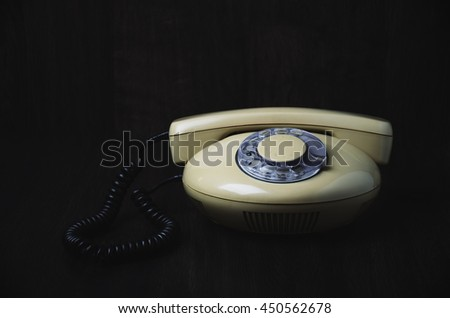 front of old-fashioned phone on a dark wooden background. horizontal format, toned image - stock photo