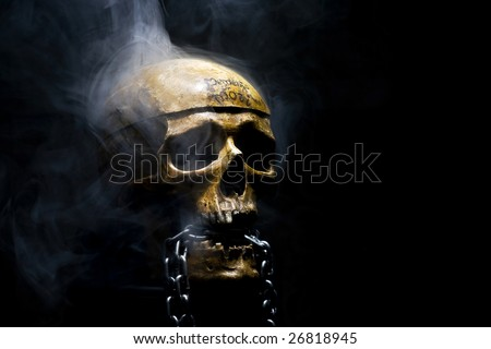 front of real skull with metal chain in smoke - stock photo