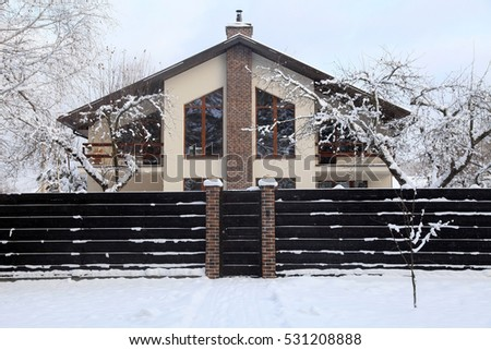 Front of suburban home under snow in winter.