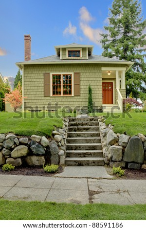 Front of the cute small green house with orange windows - stock photo