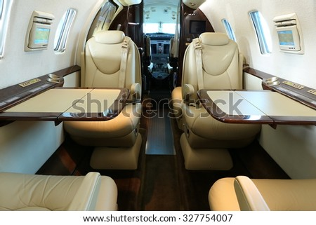 Front part of business jet cabin with open tables on both sides and lowered armrests