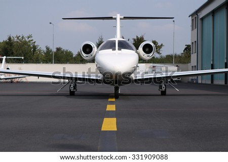 Front part of the parked small jet - stock photo
