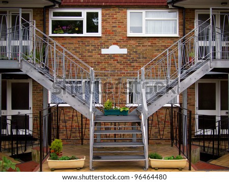 Front porch of the two connecting brick houses with flower pots and silver stairs going up left and right. Can put your text on the white sign on brick background.
