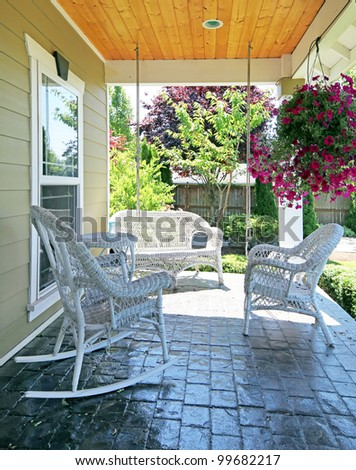 Front porch with white outdoor furniture and flowers.