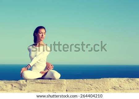 Front portrait of gorgeous young woman practicing yoga on a sunny day with amazing sea horizon on background, woman seeking enlightenment through meditation,relaxed girl performing yoga routine,filter - stock photo