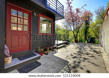 Front red door of black wood house with garden view during spring. - stock photo