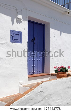 front side of typical spanish house with beautiful blue wooden door - stock photo