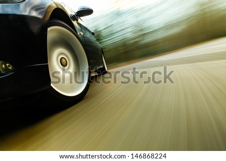 Front side view of black car in turn with heavy blurred motion. - stock photo