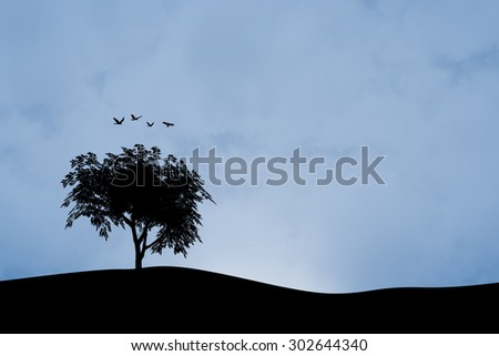 Front silhouette view of a tree on a hill by the sea or lake, on cloudy blue sky background. - stock photo