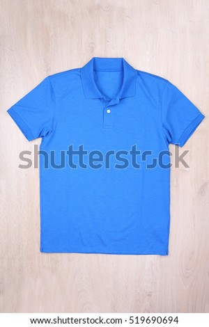 Front view blue polo shirt on wooden background