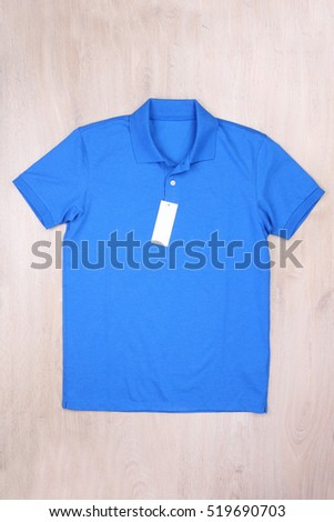 Front view blue polo shirt with label on wooden background