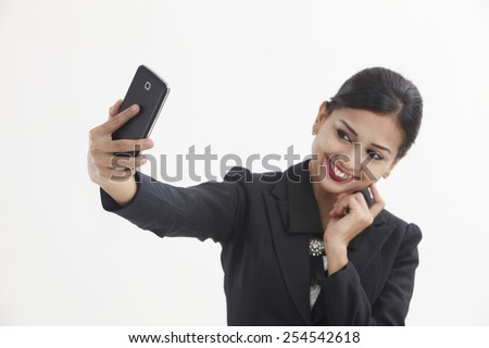 Front view business woman self portrait with smart phone - stock photo