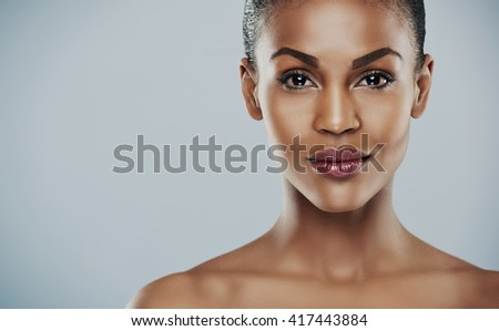 Front view close up of gorgeous African woman with calm and pleasant expression over gray background with copy space - stock photo