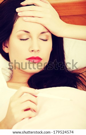 Front view face closeup of a beautiful young woman lying in bed during a cold, checking fever on thermometer, holding hand on her forehead. - stock photo