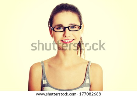 Front view face closeup of a young female caucasian teen with glasses on her face smiling to the camera, on white. - stock photo