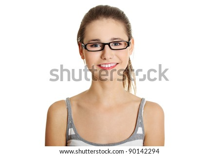 Front view face closeup of a young female caucasian teen with glasses on her face smiling to the camera, on white.