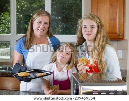Front view, looking forward, of mother and her daughters eating freshly baked cookies  - stock photo