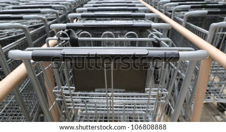 front view multiple rows of metal shopping carts outside a grocery store - stock photo