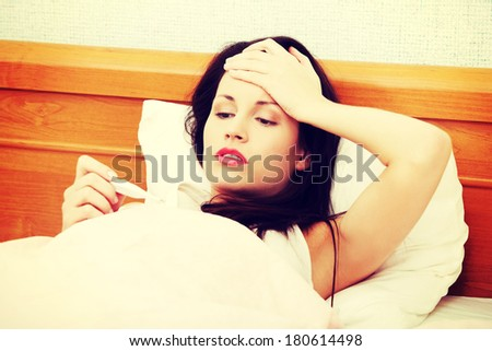 Front view of a beautiful young woman lying in bed during a cold, checking fever on thermometer, holding hand on her forehead. - stock photo