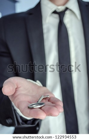 Front view of a businessman offering a key.